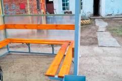 Скамья и спинка - деревянный настил с покрытием морилкой и лаком - располагается по трем сторонам