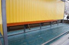 Скамья деревянная располагается практически по всей длине задней стенки