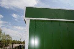 Крышу обрамляет декоративный козырек зеленого цвета с белой окантовкой