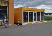 На фасадной части мини-магазина большие витринные окна и входная дверь по центру